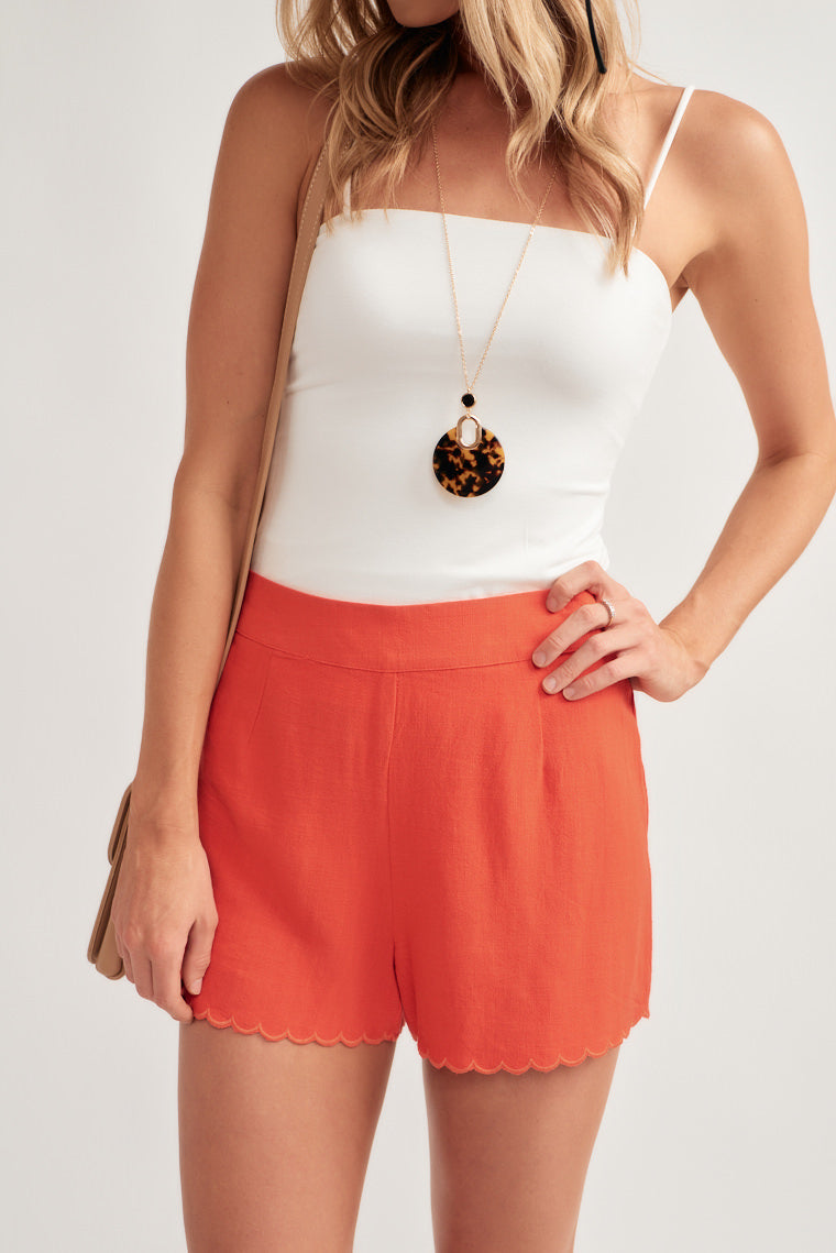 These pair of red high-rise, banded waistline shorts offer a relaxed fit with a scalloped hem for a flirty touch.
