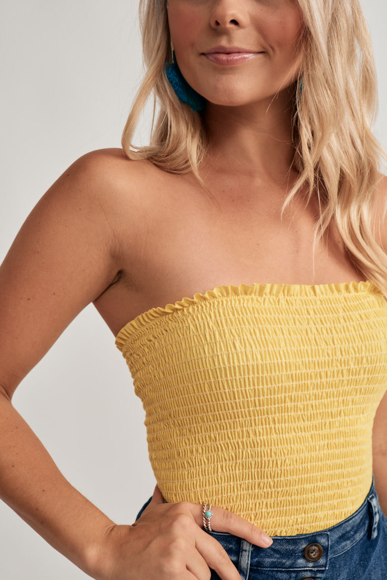 This adorable tube top in a citron hue features a strapless, ruffled neckline with a smocked silhouette and acutely cropped hem.
