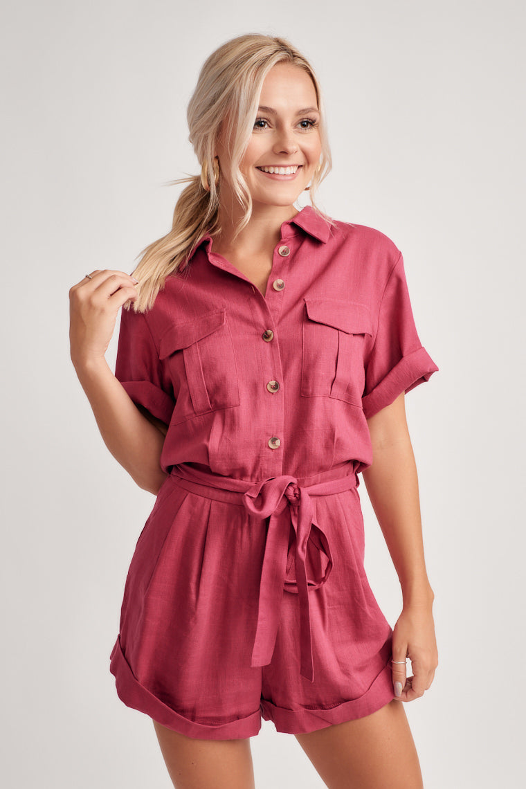 This raspberry, magenta shade romper starts with a collared v-neckline, the button-down bodice carries into a banded waistline, relaxed shorts