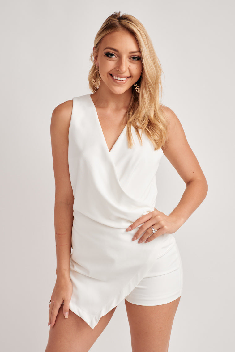 The sleeveless, surplice neckline leads to a wrap side, ruched feature over top relaxed shorts and an asymmetric hem.
