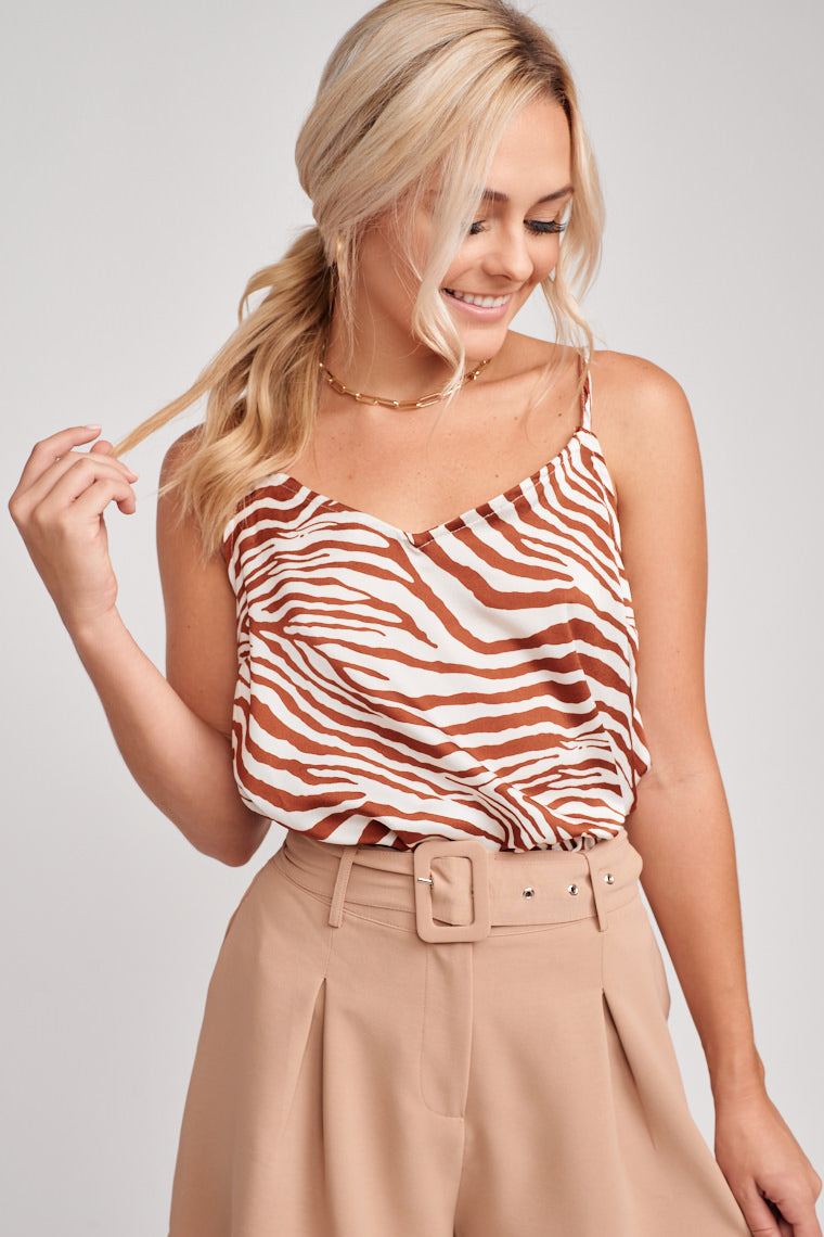 Rust zebra stripes paces across this silky fabric while skinny adjustable straps attach to a v-neckline and meet a darted yet oversized bodice silhouette.