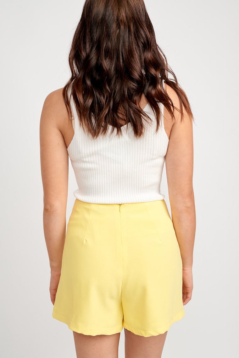 These bright yellow shorts have a fitted waistband with fabric pieces that on each side of the shorts that tie in the front and drape atop of relaxed shorts.