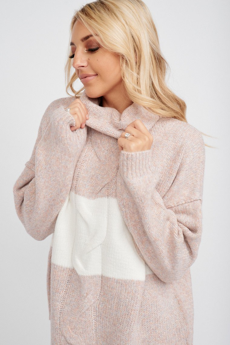 A white band crosses the bodice of this cozy cable knit sweater. Long sleeves attach to a high turtle neckline and lead down to an oversized and comfortable bodice.