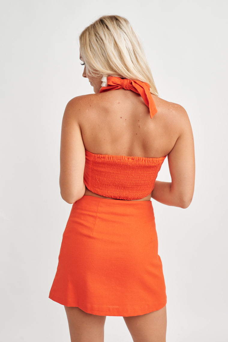 This vibrant red crop top features thick straps that come to a halter tie at the back and a straight neckline, pair with the Cheryl Mini Skirt for a matching set.