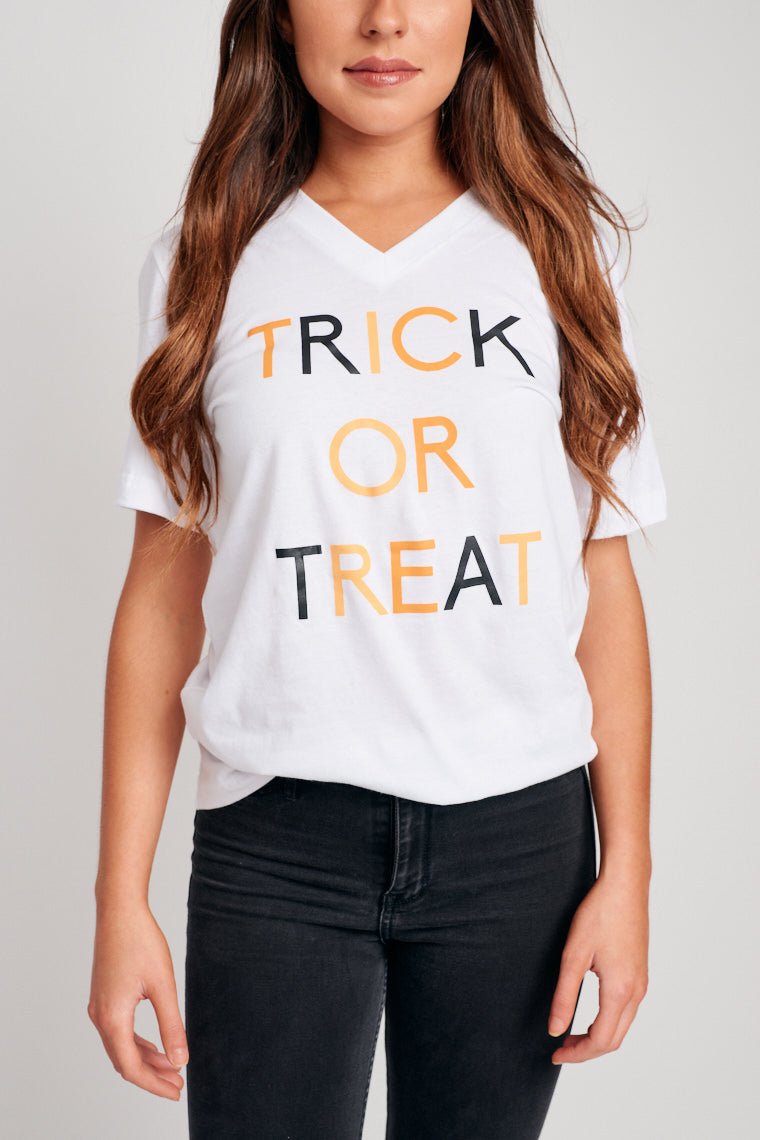 "Black and orange letters with the text ""Trick Or Treat"" lay on the relaxed bodice of this short-sleeve v-neck tee. Pair with faux leather leggings."