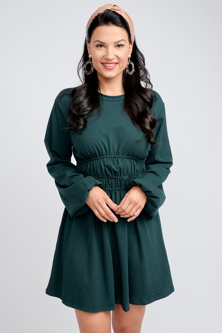 Long puff sleeves attach to a banded u-neckline on a relaxed bodice silhouette that leads to a smocked tiered waistband and flows down into a simple a-line skirt.