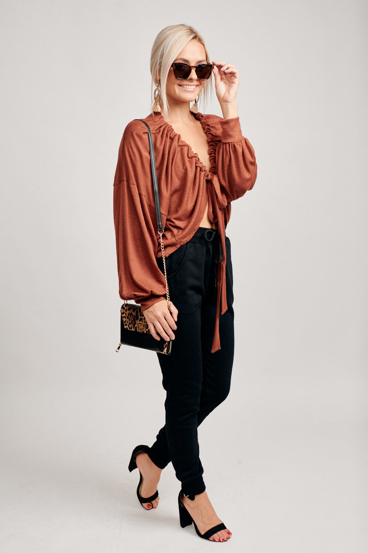 Long flowy sleeves with banded cuffs attach to a relaxed and oversized bodice with fabric drawstrings at the bottom of both sides of the opened front.