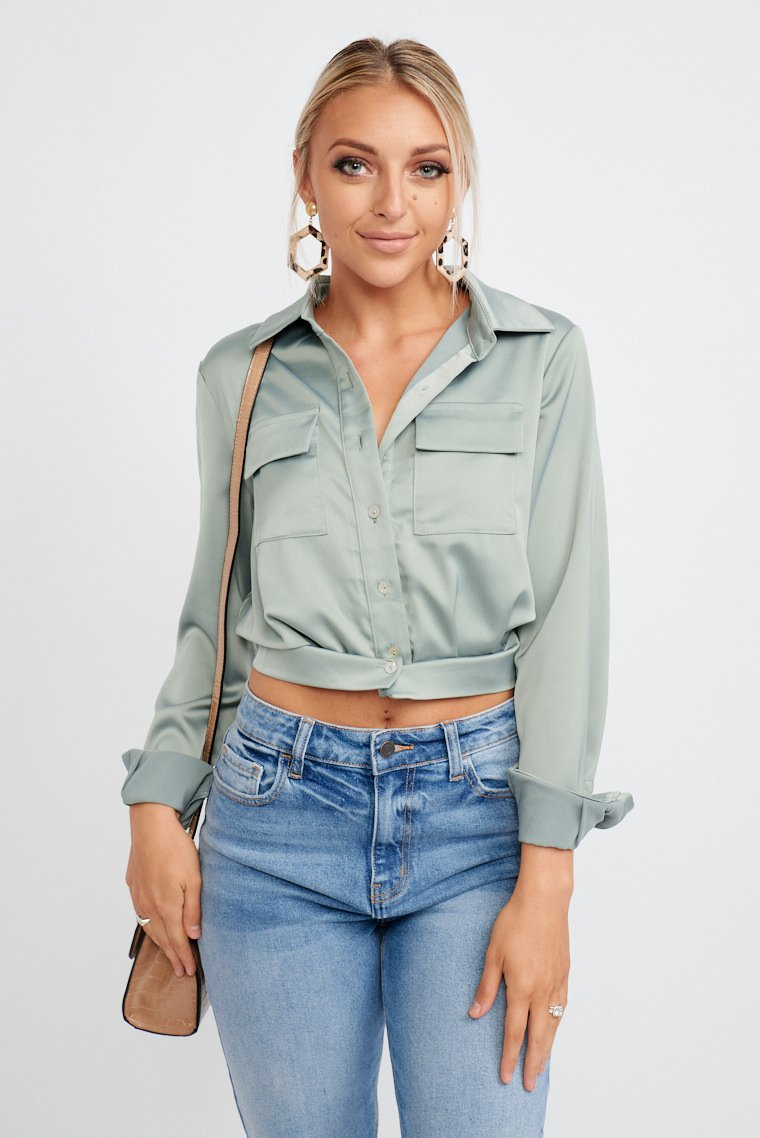 Long banded button sleeves that attach to a collared neckline and leads down button-down and cropped bodice silhouette with fabric ties that are secured at the back.