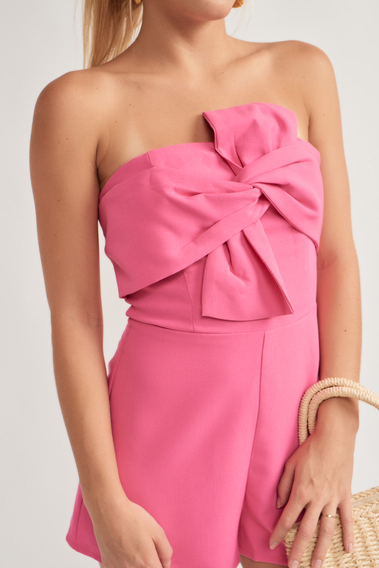 This playful pink romper features a strapless neckline with a bow bodice and fitted waistline that transitions into figure-flattering shorts.