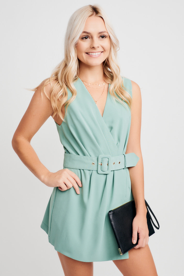 This bold romper has a surplice neckline, a relaxed bodice that meets a fitted waist with a belt, and a sheath wrap piece that overlays fitted shorts.