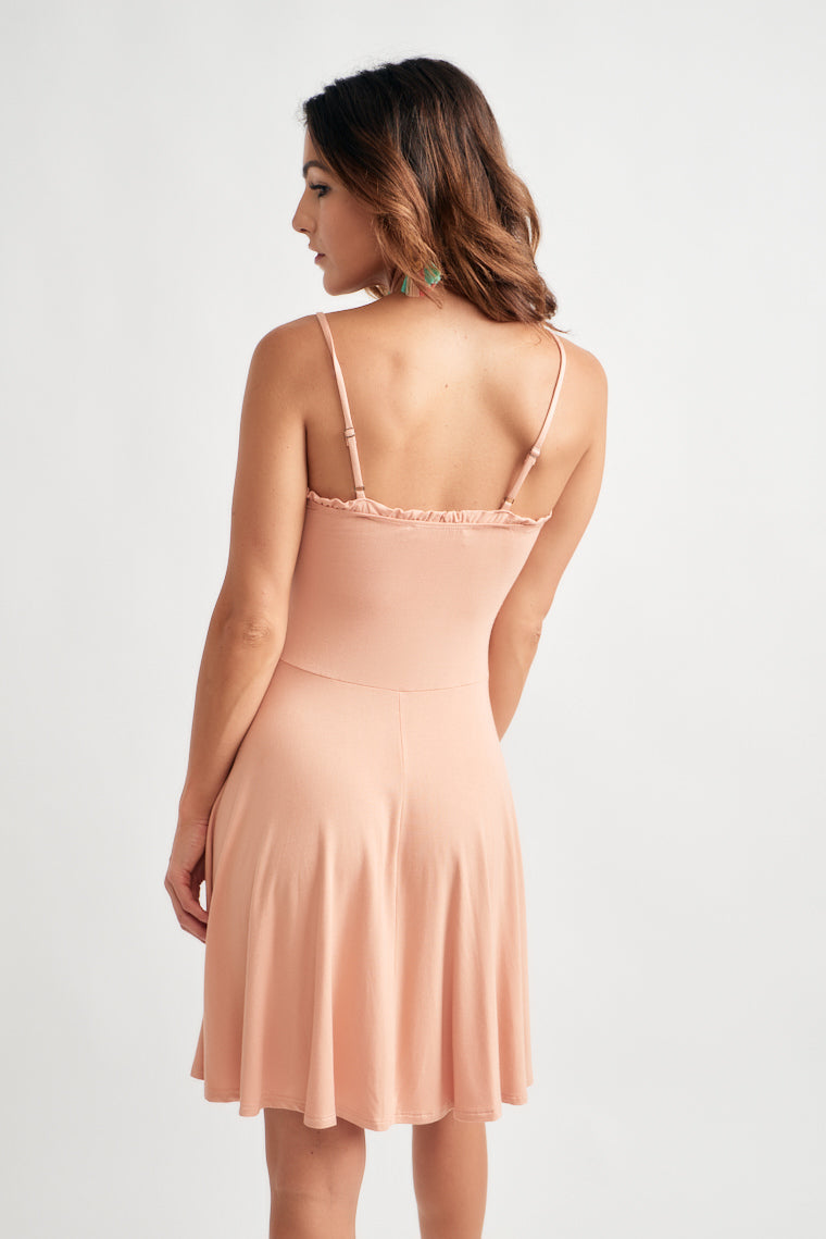 Ultra-soft and comfortable knit creates this flirty dress with adjustable skinny straps on a ruffled v-neckline with a fitted waistline that moves into a skater skirt.