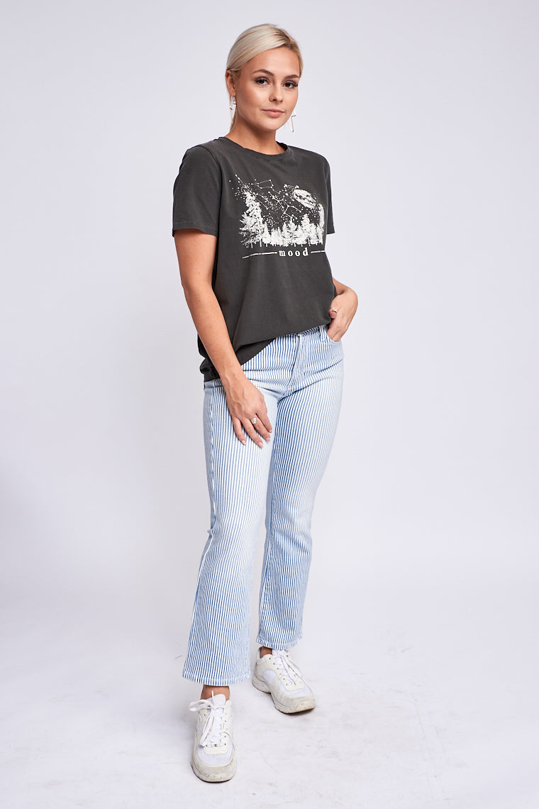 "The saying ""mood"" in stamped text underneath a forest graphic with stars and a large moon while on a crew neckline, short sleeves, and a relaxed fit bodice."
