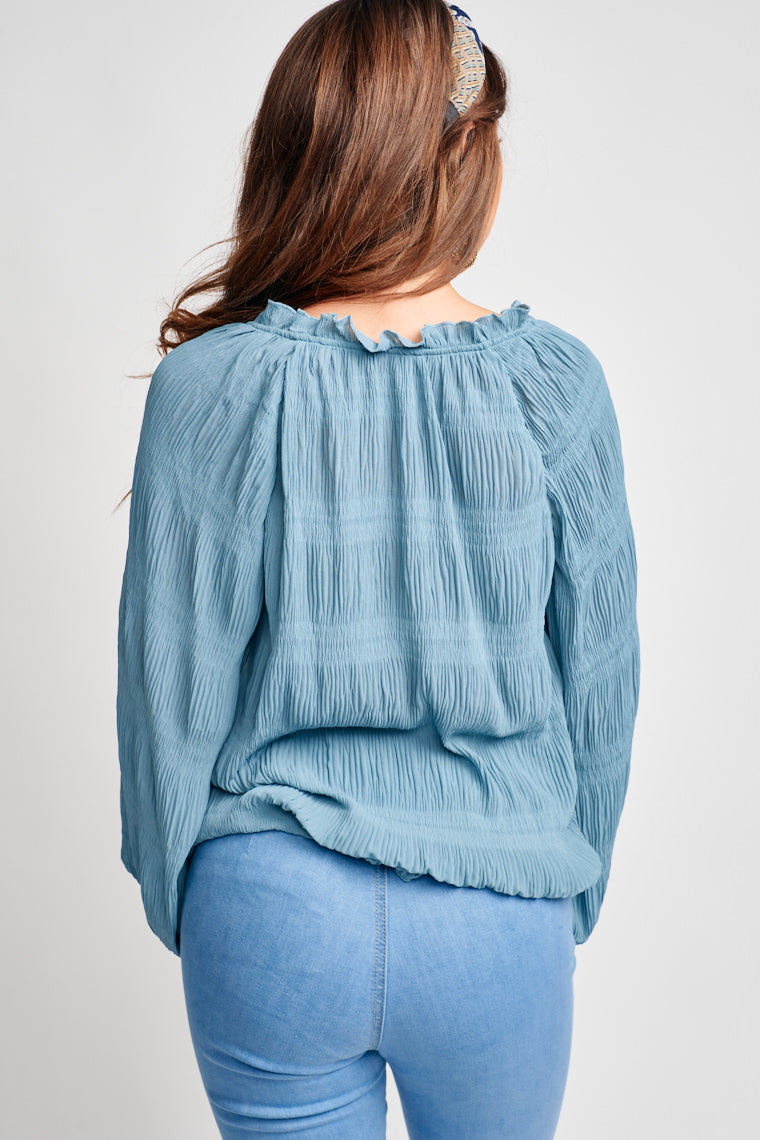 Long puffed sleeves with an elastic cuff that is attached to a ruffle v-neckline with a tassel tie that could be secured at the neck and an oversized relaxed bodice.