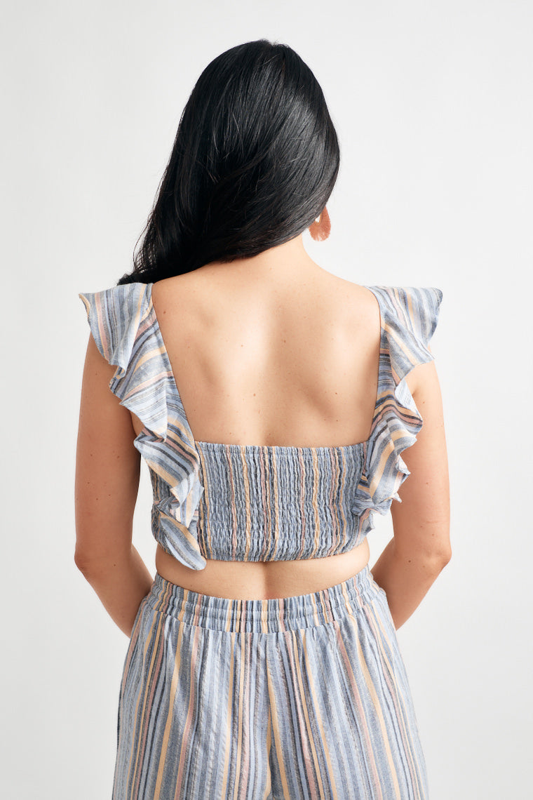 Shades of blue, pink and tan stripes printed on the ruffled sleeves that flow down the side, ruched bodice and a smocked back.