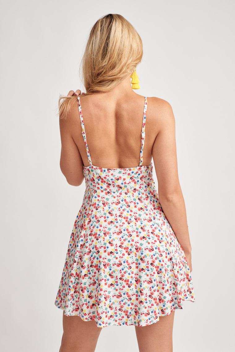 Floral, lightweight sundress with adjustable skinny straps support a triangle neckline with a banded waistline that flows into a flirty and flowy skirt.