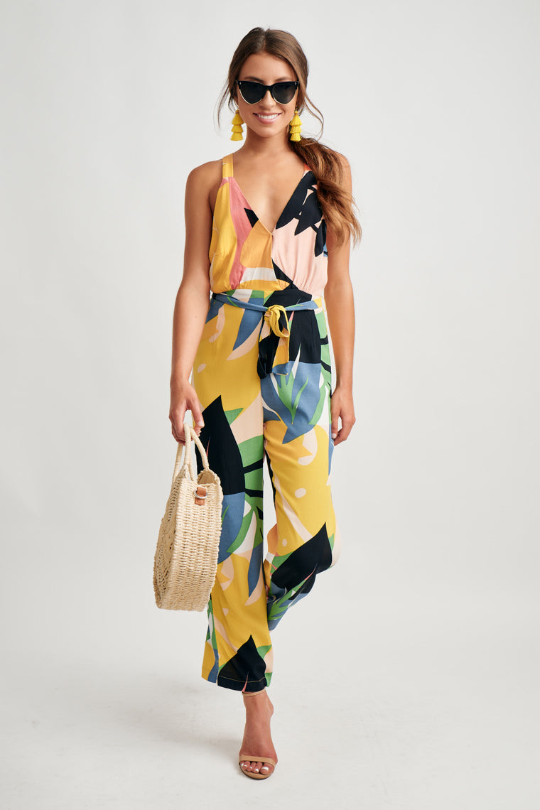 Tropical leaves in multiple colors lay overtop one another to form this unique summer print that decorates this jumpsuit offering thick straps on a surplice neckline with a criss-cross, open back.