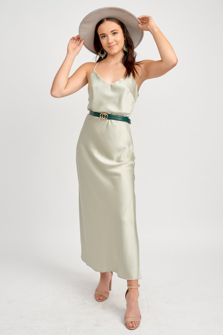 Thin adjustable straps attach to a v-neckline on a fitted and darted bodice and lead down to a sleek straight skirt with a side slit that reaches mid-calf.