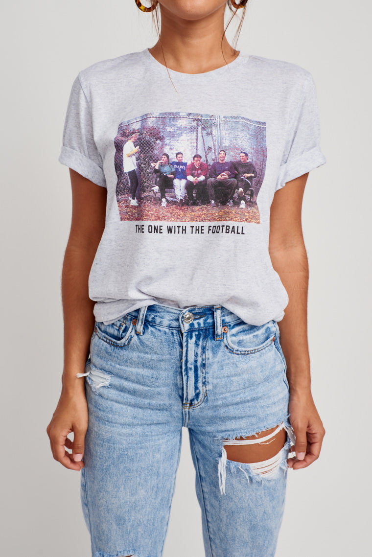 "This oversized and comfy graphic tee displays the iconic group in their casual gameplay attire on a bench with ""The One With The Football"" in black text underneath."