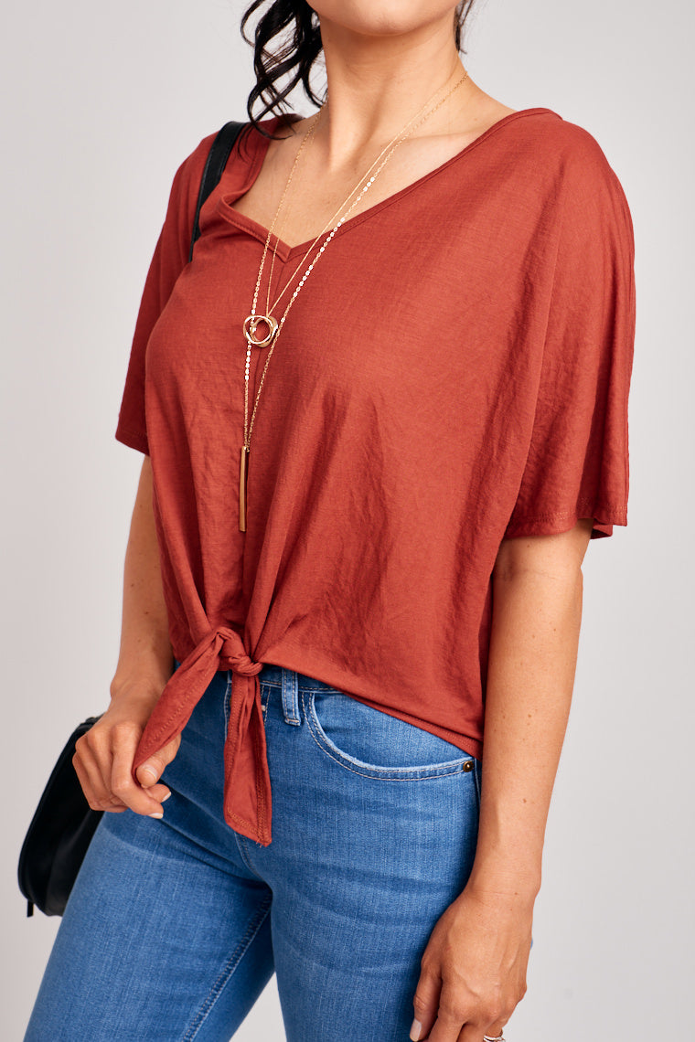 Short sleeves attach to a banded v-neckline and oversized and relaxed bodice silhouette with a tie front hem. Pair with jeans, a layered necklace, and white sneakers.