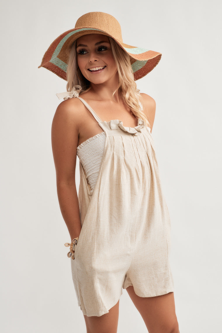 This lightweight, beige overall style romper starts with adjustable tying straps on a pleat, ruffle neckline that moves into a sleeveless, relaxed silhouette.