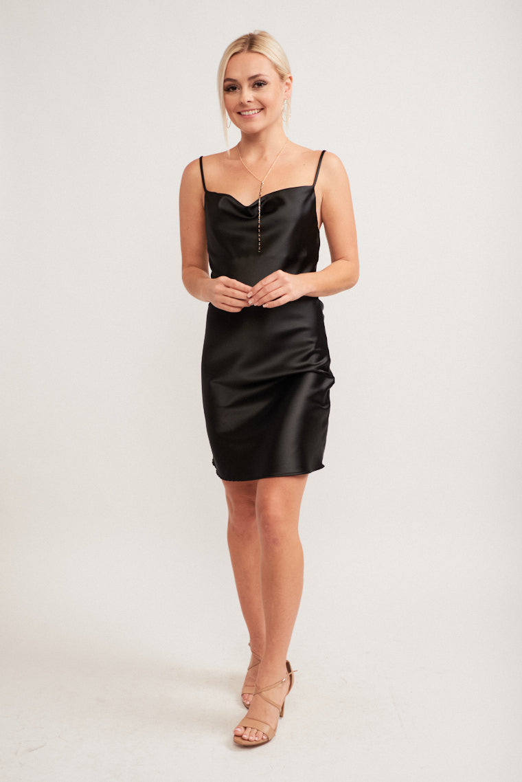 This satiny fabric dress has thin straps that attach to a cowl neckline with a fitted bodice and skirt silhouette.