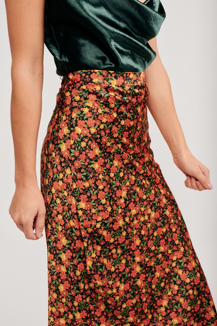 Multi-colored flowers cover this vibrant midi skirt. This skirt has an elastic waistband that leads to a straight silhouette and has a gentle flare hemline.