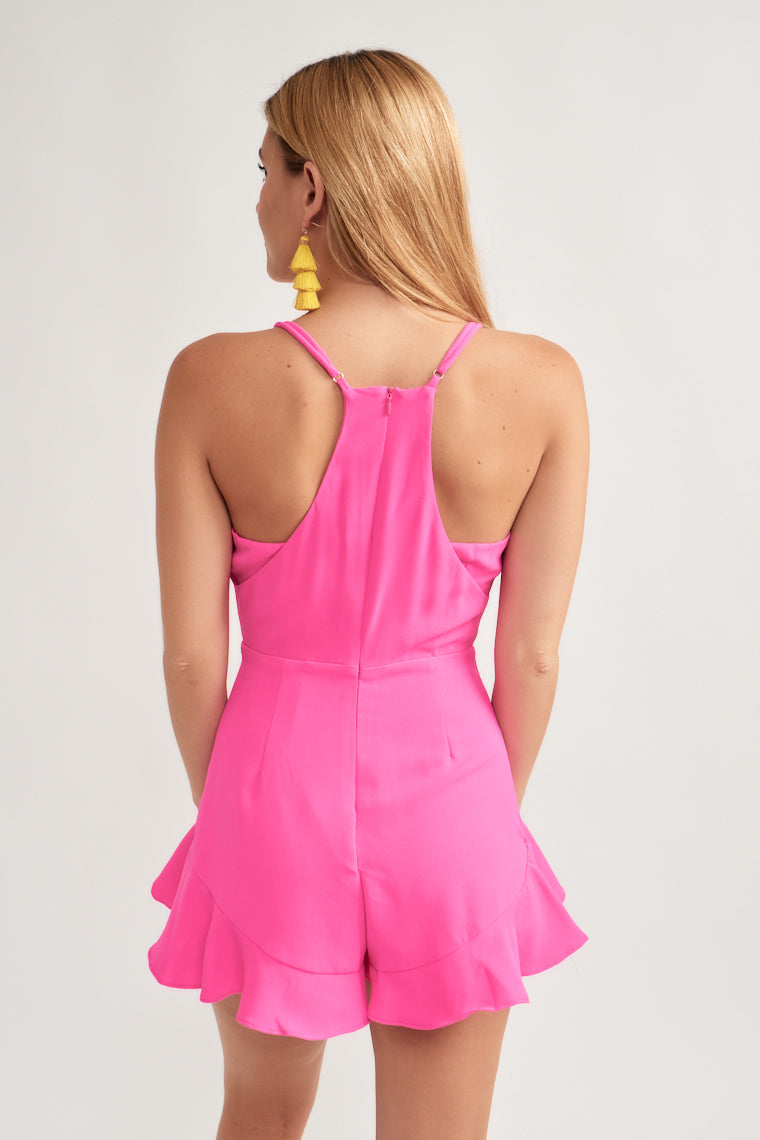This vibrant pink romper offers adjustable skinny straps supporting a racer back and front v-neckline. The darted bodice moves into a fitted waistline with cascading ruffles down the tulip shorts to the ruffled hem.