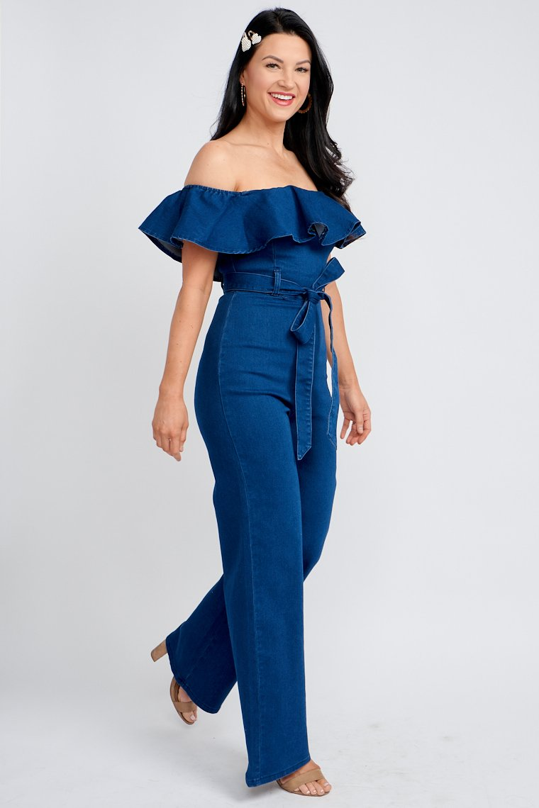 This off the shoulder ruffled jumpsuit has a fitted bodice with flounce hem that adds fullness and leads down to a fitted waist with belt loops and wide pant legs.