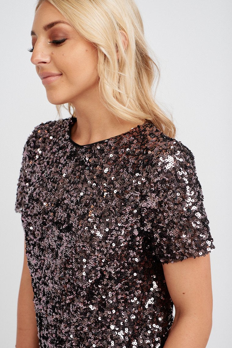 Shimmering purple sequins cover this short-sleeved dress that has a high rounded neckline and t-shirt style silhouette. Pair this with nude strap heels.