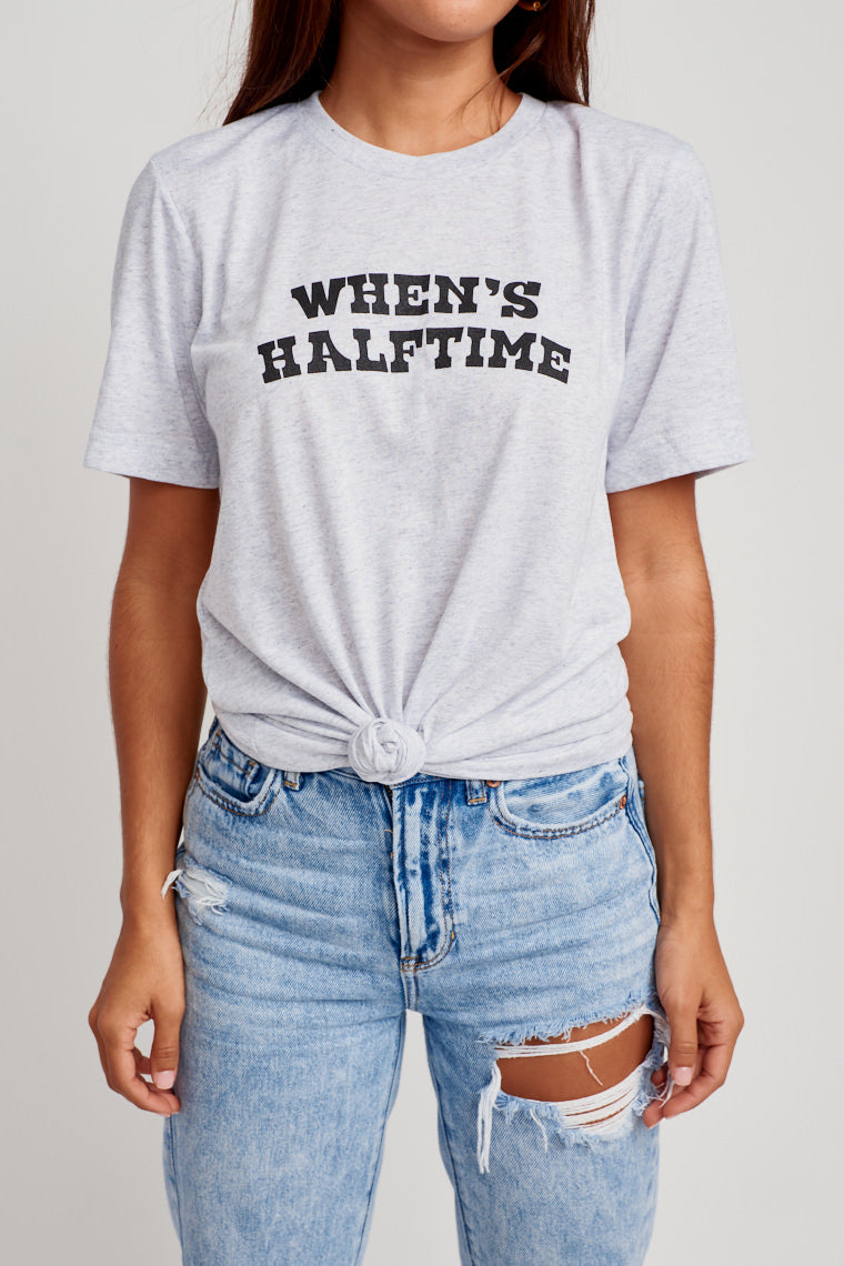 "This oversized and comfy grey tee has ""When's Halftime"" in black text across the chest. Style by tying a front knot with denim shorts for a cute game day look!"