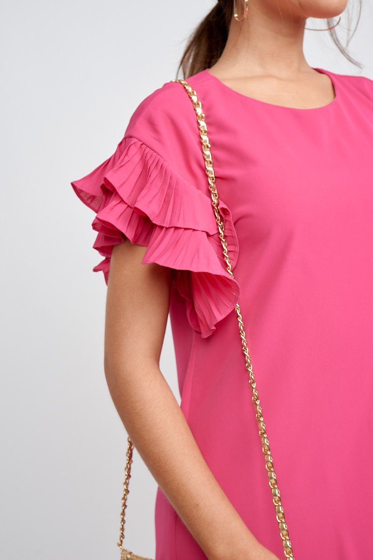 This bright magenta dress has short pleated flutter sleeves that attach to a high u-neckline goes down to an oversized shift dress silhouette.
