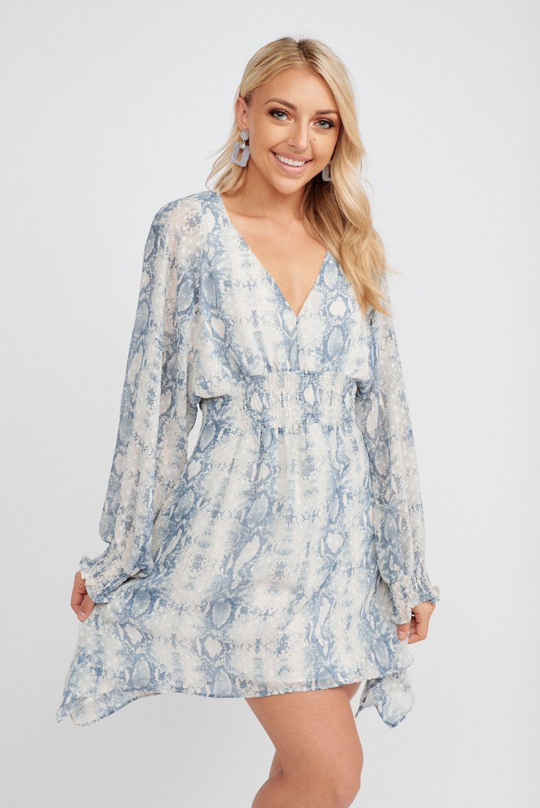 Long smock cuff sleeves attach to a v-neckline on a relaxed fit bodice with a smock center front at the waist that leads down to a flowy and asymmetrical cut skirt.