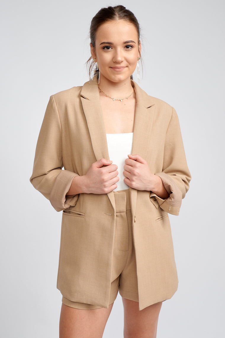 Long button cuff sleeves attach to a collared neckline on a darted yet oversized-fit one-button bodice, sleek faux-pocket panels at the sides of the blazer as a detail.