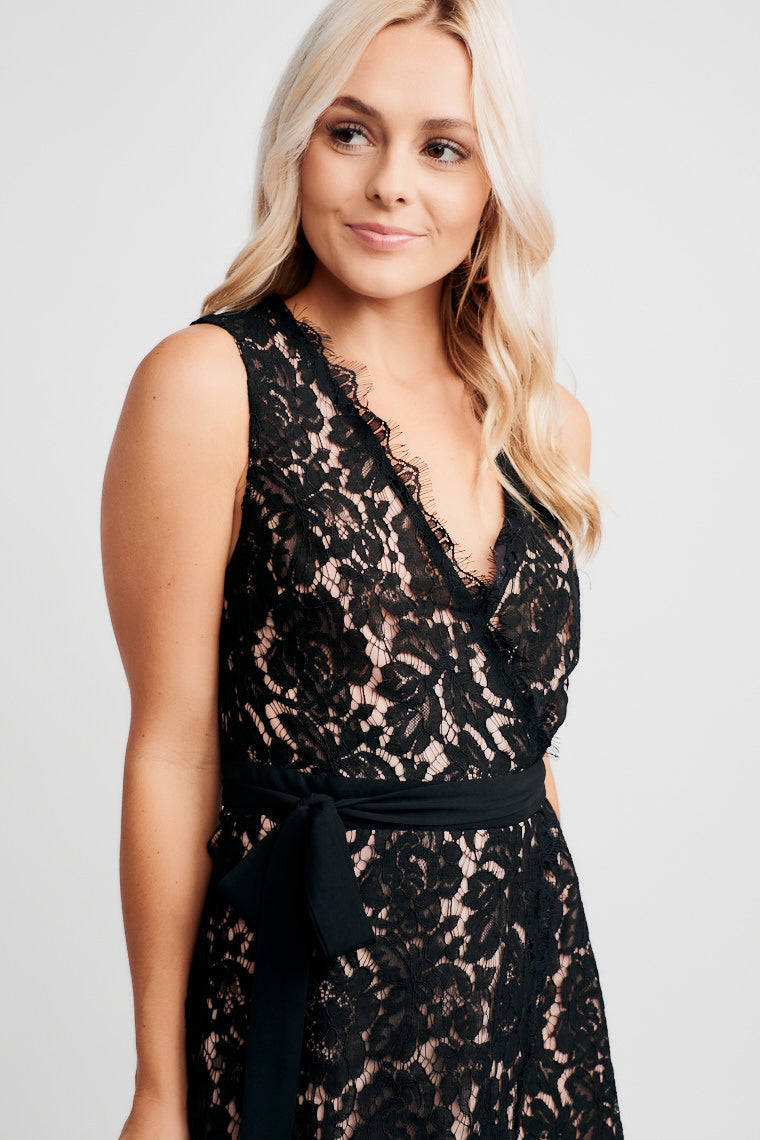 This black lace dress has a surplice neckline with lace scallops at the hem. Its wrap skirt meets a black ribbon waistband and ties at the side for an elegant and polished look.