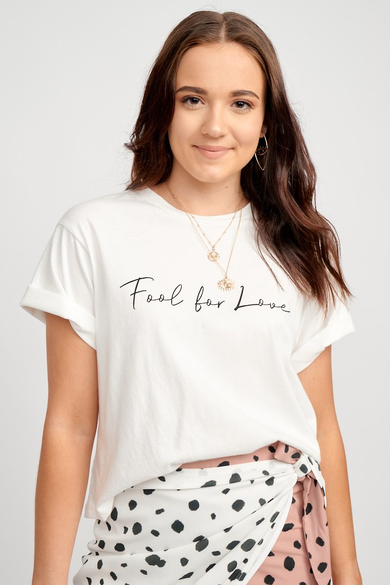 "Short sleeves attached to a u-neckline and leads to a cropped yet oversized bodice silhouette. The words ""Fool for Love"" are in thin black cursive script across the chest."