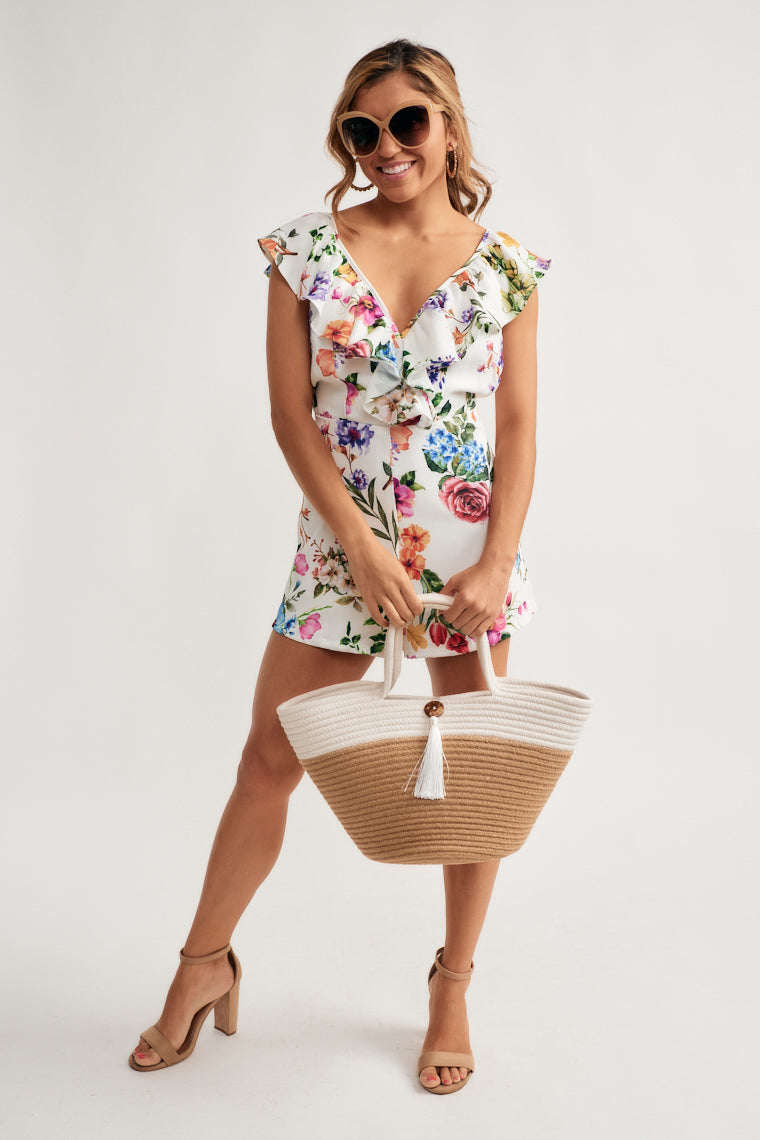 Vibrant florals bloom this delightful romper featuring ruffled skinny straps that move into the v-neckline and wrapping to the side waist. Relaxed shorts with an open tying back finish off this number