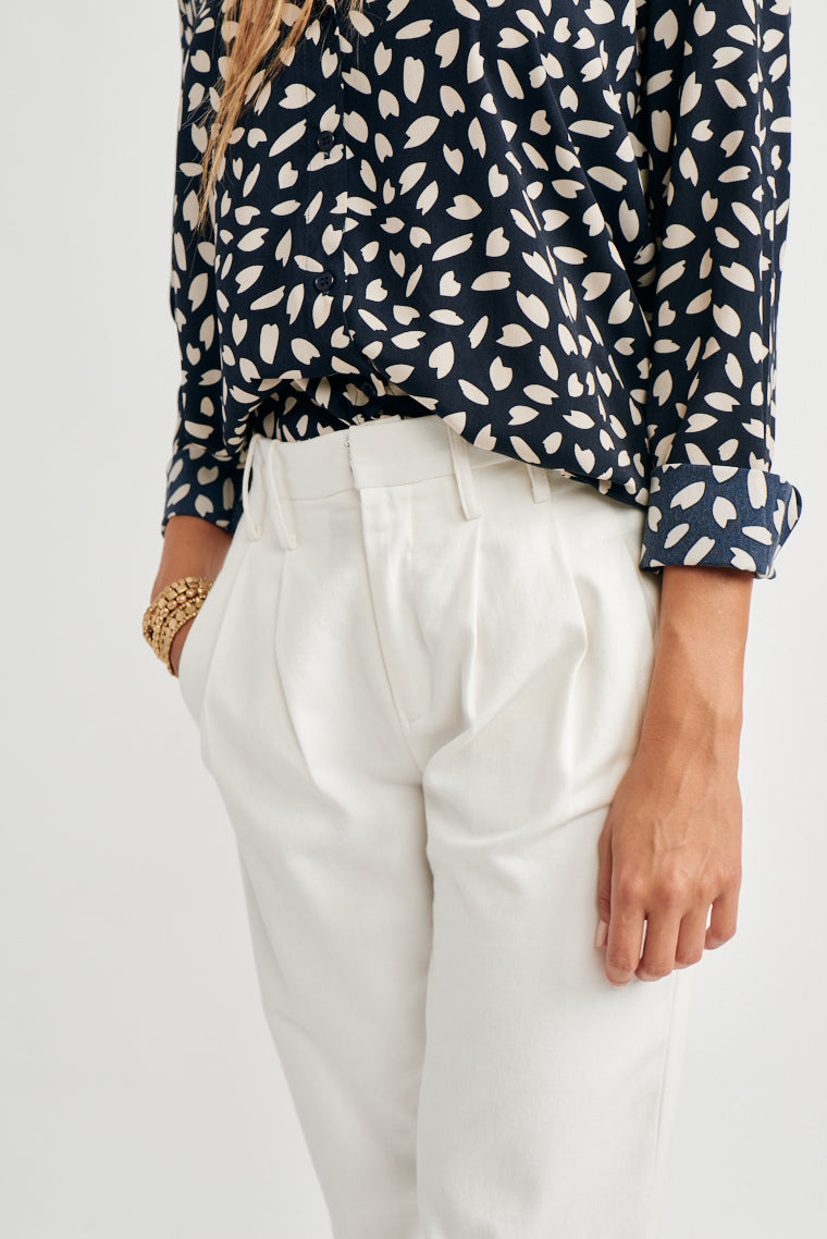 This sleek chiffon blouse with a navy and off-white print has collared neckline, relaxed bodice with a button-down silhouette and long sleeves with button cuffs.