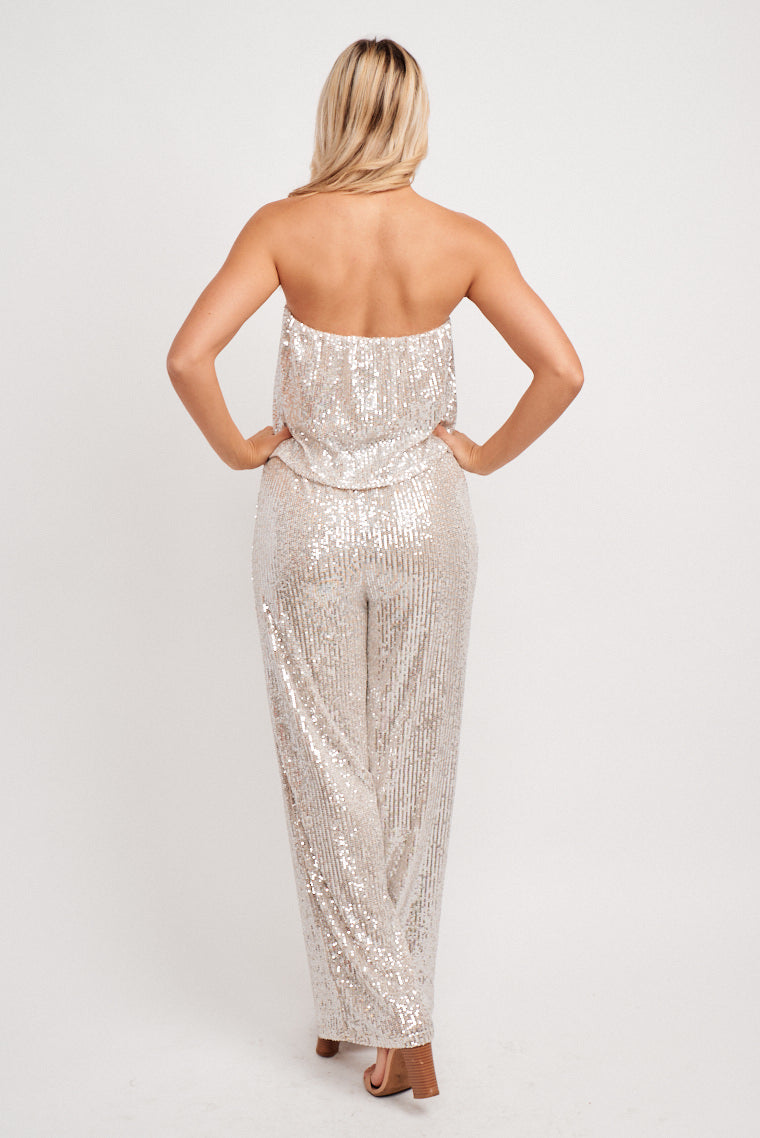 Silver mini sequins cover the fabric of this jumpsuit. This strapless jumpsuit has a flowy and flounced bodice leading to an elastic waistline that flows into wide pant legs.