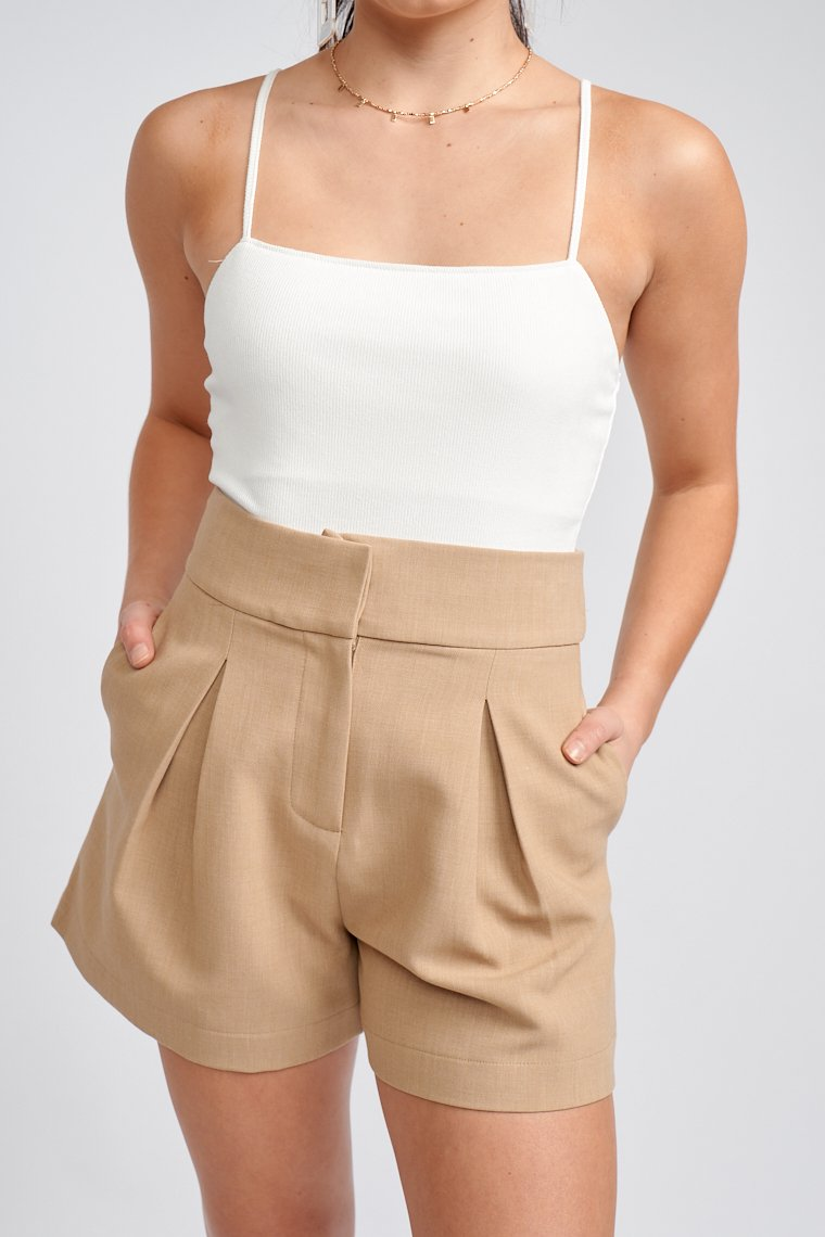 These shorts have a fitted waistband that leads down to a zipper fly next to a pleat detail at the front of each pant legs and goes into relaxed shorts with a clean hem.