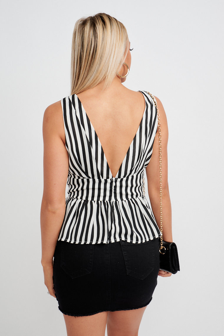 Bold black and white stripes across the fabric of this lightweight top. Medium straps lead into a deep v-neckline into a banded waist and flares out into a peplum-style hem.