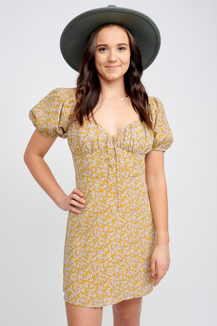 Short elastic cuff sleeves attach to a sweetheart neckline and shirred bust panel with a tie at the center of a fitted bust which then flows down to a simple and relaxed skirt.