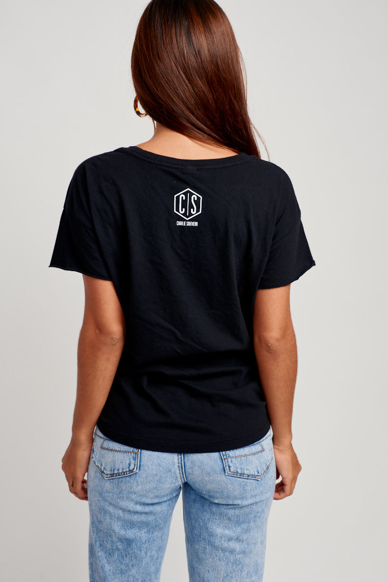 "This oversized and comfy black tee has ""I Just Hope Both Teams Have Fun"" in white text across the chest. Style by wearing denim shorts and sandals for a tailgating outfit."