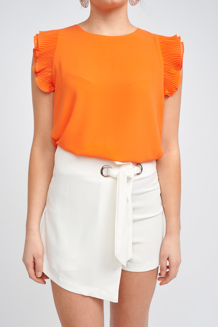 Fitted waistband that leads down to grommet ring details with a fabric tie that secures at the waist and flows down to an asymmetrical skirt panel atop of comfortable shorts.