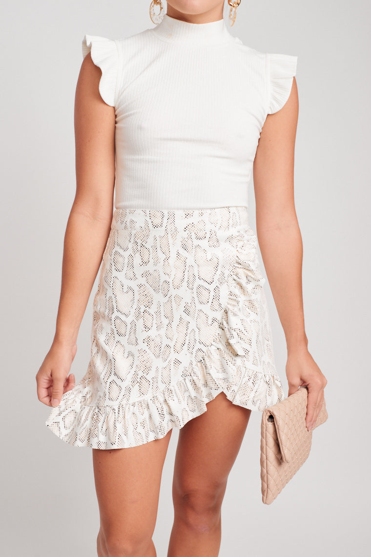 Light taupe and black snakeskin skirt that has a fitted waistband and leads to a faux wrap and ruffled asymmetrical hem which crosses over the front of the skirt.