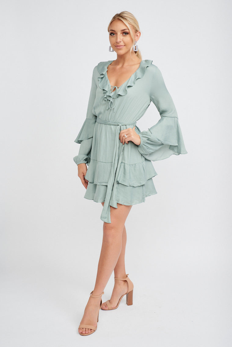Asymmetrical ruffle down the sleeves attach to a v-neckline with a ruffle hem and thin tie on a relaxed bodice leads to an elastic waistband and flows down to ruffled skirt.