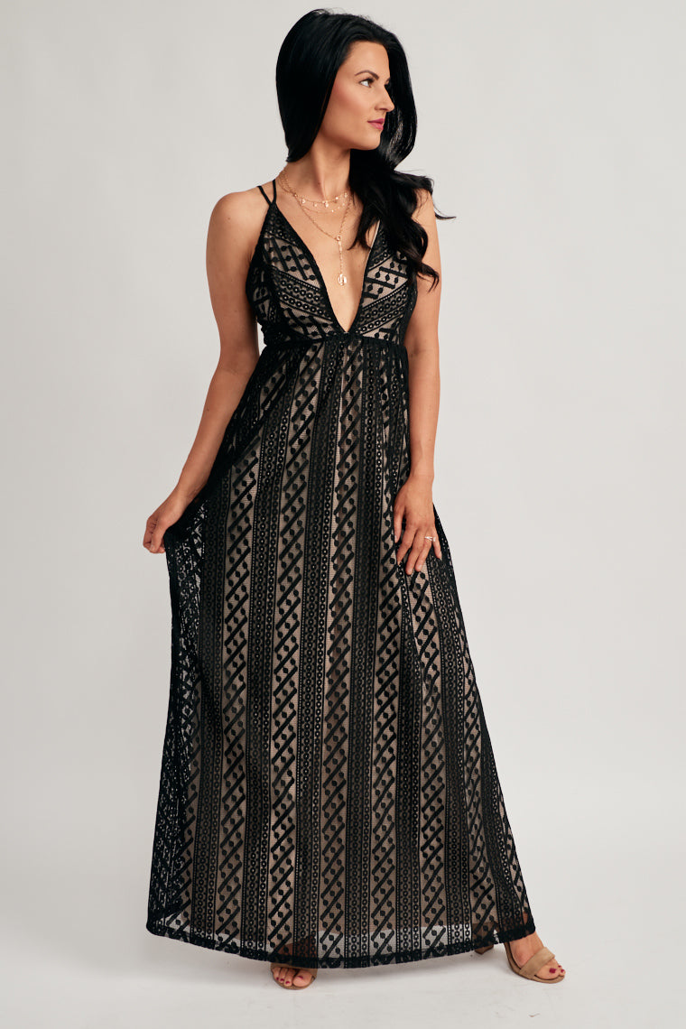 Black lace with a nude underlying shapes this elegant maxi dress with adjustable thin straps on a plunging neckline, empire waist, and flowy maxi skirt.