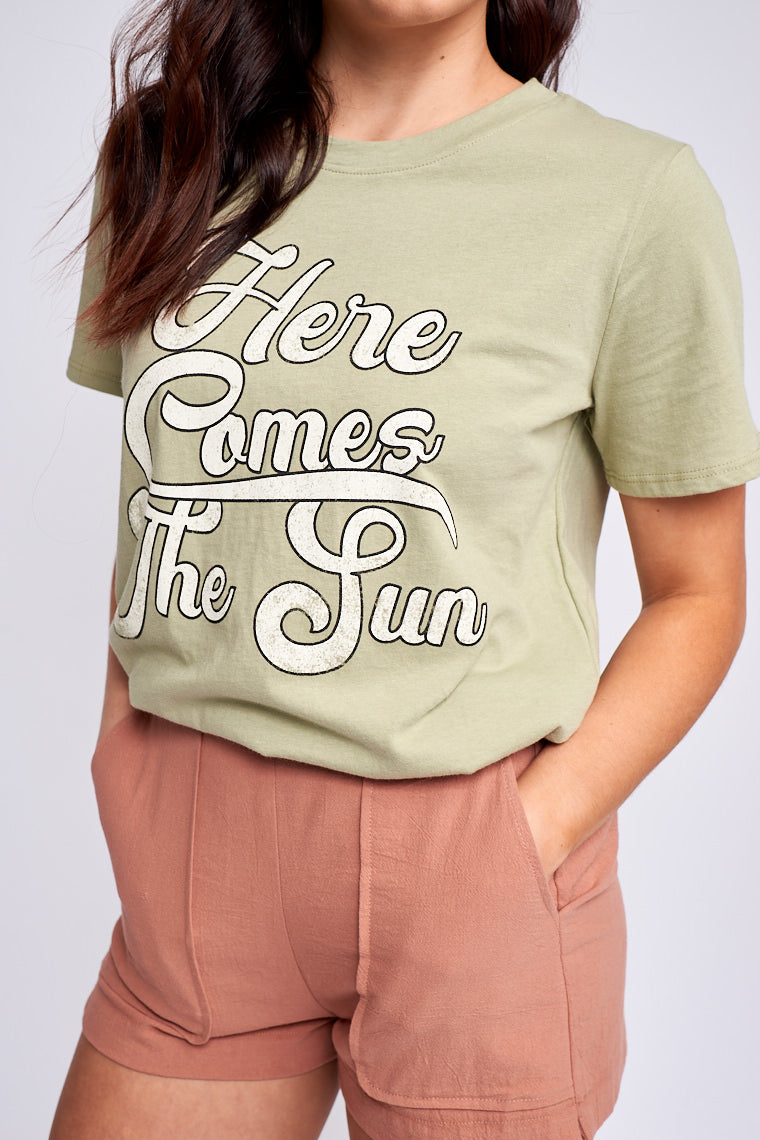"Super cozy graphic tee has the saying ""here comes the sun"" in fun illustrative writing on top a crew neckline, short sleeves, and a relaxed fit."