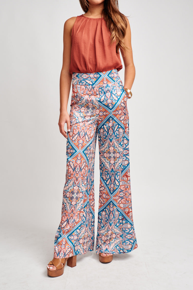 These multi-colored pants are high-rise with a thick fitted waistband and lead to pockets and then loose straight pant legs. These pants feature a zipper and hook and eye closures.