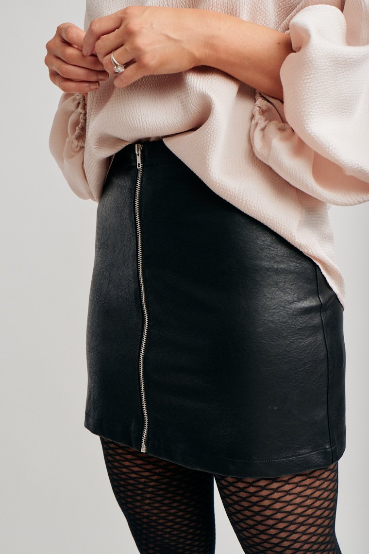 Add some edginess to your look! This faux leather skirt has a fitted waistband that leads to a zipper down the front of a fitted mini pencil skirt.