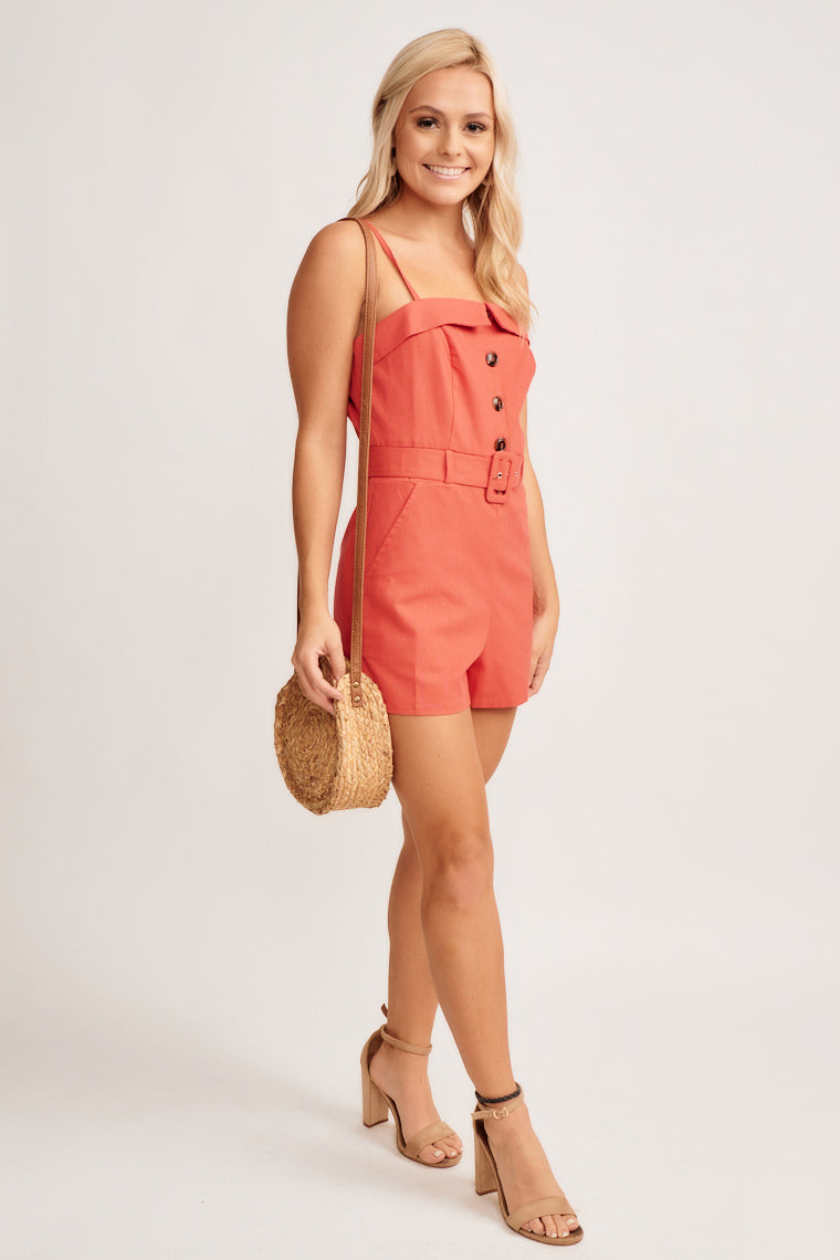 Straight neckline, a darted button detailed bodice held by skinny adjustable straps, with straight-cut shorts, fitted waist with loops to support a belt.